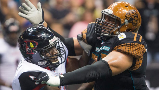 Anttaj Hawthorne of the Arizona Rattlers tries to power past Orlando's Will Maxwell in an Arena Football League game on June 20, 2015.
