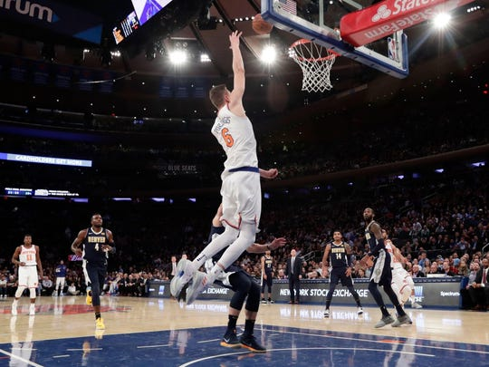 Knicks' Kristaps Porzingis catches a lob pass from Courtney Lee for a dunk Monday in New York. The Knicks won 116-110.