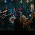 """Tallahassee artists Jim Roche and Alex Kleinbard, center, dance in front of the stage while Meryl Streep, right, and Rick Springfield, left, perform live in a scene from """"Ricki and the Flash."""""""