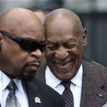 Actor and comedian Bill Cosby, right, smiles as he arrives for a court appearance Wednesday in Norristown, Pa. Cosby was arrested and charged with drugging and sexually assaulting a woman at his home in January 2004. A judge will decide whether to dismiss a sexual assault case against the comedian over an unwritten promise of immunity that a former prosecutor says he gave Cosby's now-deceased lawyer.