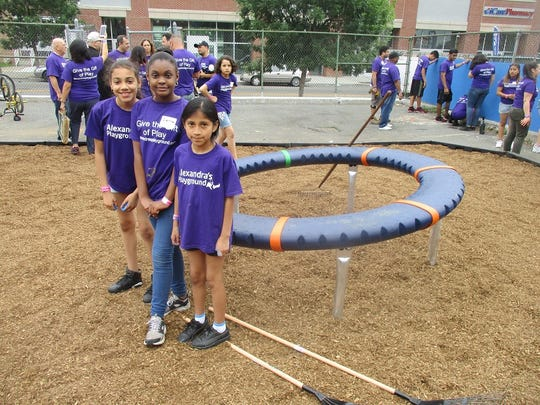 Students Gianna Leslie, Shaniya Mott, and Yarelie Guerrero, at the construction of the new playground at Paterson's School 8.