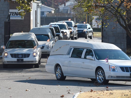 A funeral procession arrives at Oak Hill Cemetery after