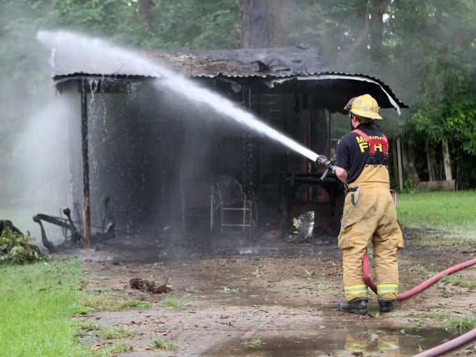 Monroe firefighters work the scene after a shed and a tree caught on fire Tuesday near Georgia and Parker streets in Monroe. Lightning is suspected to be the cause of the fire, although it is still under investigation.