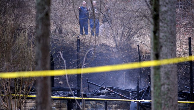 Fire investigators inspect the remains of a home destroyed by an overnight fire off Owens Cove Road Friday morning March 20, 2015.