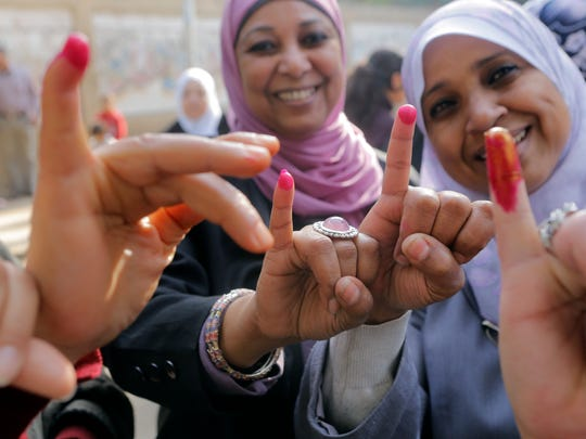 Egyptian women show their inked fingers after casting their votes at a polling station in Cairo, Tuesday, Jan. 14, 2014.