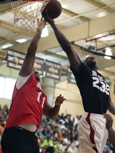 Former NFL players Dante Culpepper, left, and  Jevon Kearse battle for the rebound during a celebrity basketball game at Bishop Verot High School on Saturday.