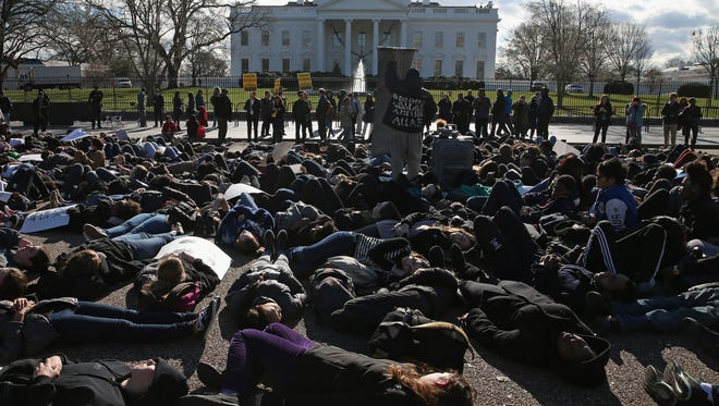 Students from The School Without Walls lie down on Pennsylvania Avenue during a protest in front of the White House on Dec. 17, 2014.