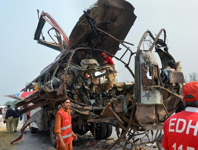 Rescue workers search a destroyed bus after a bomb attack on Sept. 27 in Peshawar, Pakistan. Eighteen people were killed when a powerful bomb tore through a bus carrying government workers in northwestern Pakistan.