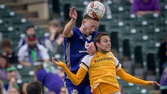 Louisville City's Sean Totsch (4) and Nashville SC's Robin Shroot (8) collide during the home opening game at Slugger Field in Louisville, Ky, March 17, 2018.