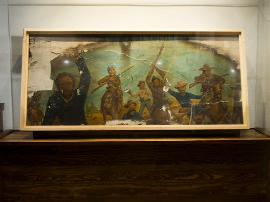 A mural from the former Alamo Steakhouse that survived the wildfires was saved and is now displayed inside the new Alamo Steakhouse building.