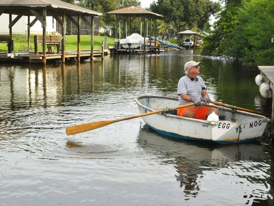Owen McElroy rows along a canal often plagued by shallow water. Residents in Indian River Isles near Rockledge have trouble