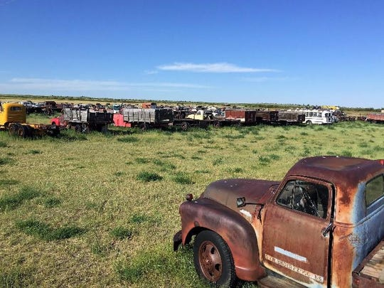 A GMC truck, bottom right, sits in the Rustless in Montana yard east of Cut Bank.