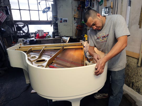 Cesar Ortega cleans a Yamaha Baby Grand Piano at the Craftsman Piano workshop in the YoHo Arts complex on Nepperhan Avenue in Yonkers.