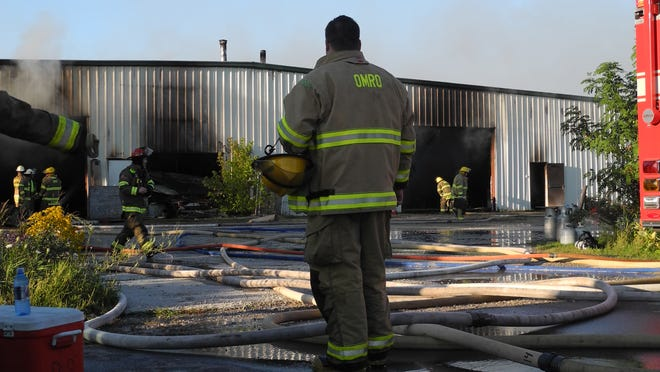 An Omro-Rushford firefighters takes a break as crews continue to fight a fire inside CC&R Wood Products Tuesday in Omro.