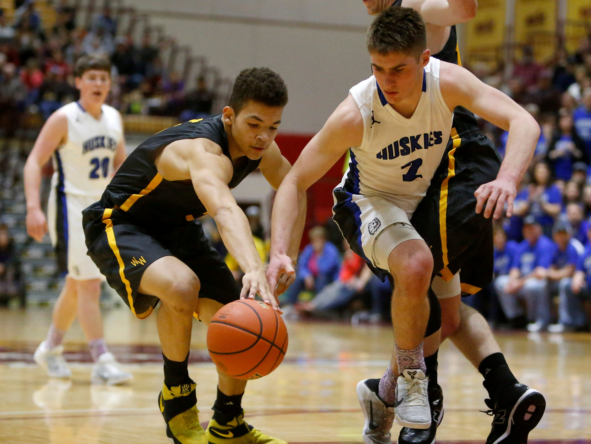Wolsey-Wessington's Lynden Williams, left and Bridgewater-Emery's Jamin Arend, center, go after the ball as the Warbirds' Tyler Babcock, right, avoids a foul during Saturday's championship game at the South Dakota Class B Boys Basketball Tournament at Wachs Arena.
