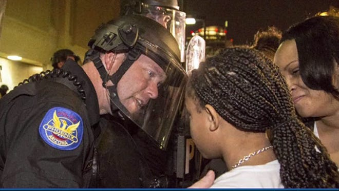 During a Dec. 8, 2014, protest, an unidentified Phoenix police officer tells Aiyana Brisbon, the daughter of police shooting victim Rumain Brisbon, that he's sorry.