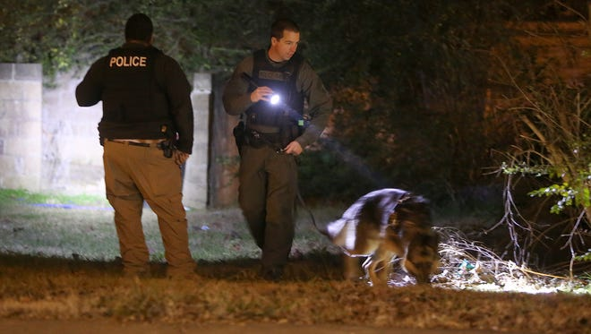 Police officers search along Hays Avenue, between Carter and Orchard streets, in East Jackson, following a shooting on Friday evening.