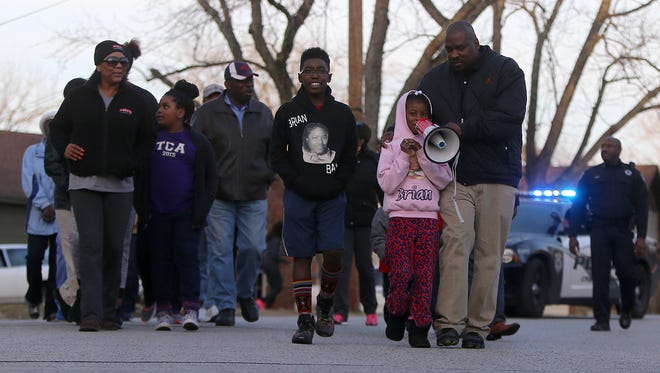 Jackson City Councilman Johnny Dodd holds the megaphone for Briana Banes as they walk in an anti-crime march down Carolane Drive on March 4.