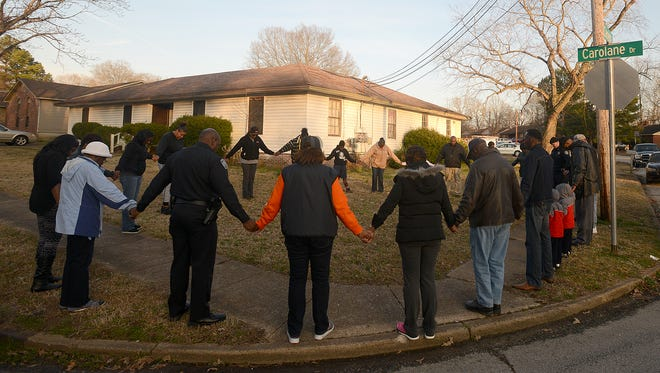 A prayer circle is formed at the corner of Carolane Drive and Camelot Cove before the start of an anti-crime march on March 4.