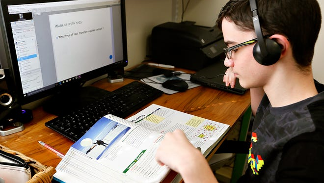 Ethan Moore, 14, who has been diagnosed with Asperger syndrome, looks up an answer in his Earth Science book during his Pennsylvania Cyber Charter School class at his home in Wrightsville, Wednesday, April 6, 2016. Moore has done well in his cyber classes since being pulled from public school because the standardized testing was overwhelming for him. Dawn J. Sagert photo