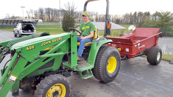 Austin Williams, of East Berlin accomplishes the backing of the tractor and manure spreader into the stall.