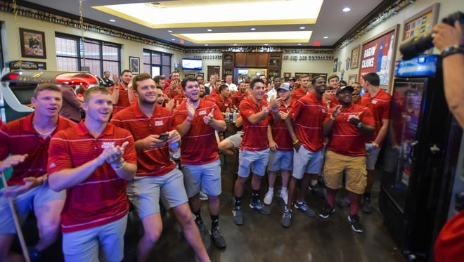 The UL Ragin' Cajuns baseball team reacts to seeing their school's name on the NCAA Regional bracket on ESPN on Monday.