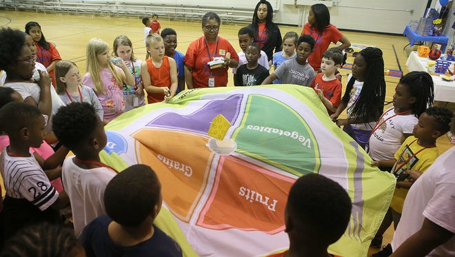 Kids play a game where they use a parachute to move items to the correct food group Friday during Westwood Day Camp's kickoff bash.