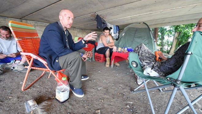 Casey Bowling, 35, second from left, gives advice to other residents beneath the College Avenue bridge, in York where he says he's been living for about five months.