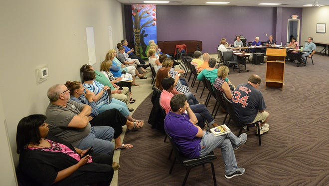 People attend a board meeting at the Milan Special School District Central Office where a new director of schools was selected.