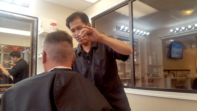 In Lovely Hair & Nails, barber Tam Nguyen cuts a customer's hair. A native of South Vietnam, Nguyen has cut hair in Lebanon County for 15 years.