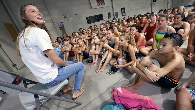 Rio Olympic swimmer Hali Flickinger talks with swimmers after practice during a homecoming at Graham Aquatic Center-YMCA Monday. Flickinger trained in the program for many years.