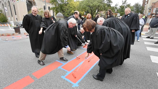 "A group of York County judges gather to mark the doorway of the original courthouse on Continental Square in York Sunday October 9, 2016. The ""Square on the Square"" history based art project outlines the footprint, focus attention on the Articles of Confederation and York's building of the United States."