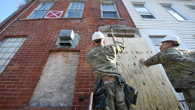 Sgt. Kevin Gendell, left, and Roberto Margarin with The Pennsylvania Army National Guard secures a building in the 200 block of North Pine Street to help the City of York secure some of the houses that have red-and-white 'X' signs on them.