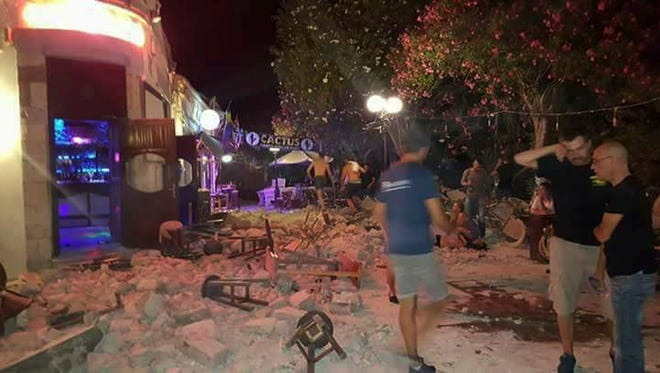 Tourists are pictured standing outside a bar after an earthquake struck the Greek island of Kos on Friday.