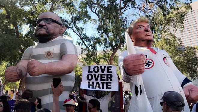Blowup dolls are erected of former Maricopa County, Ariz., sheriff Joe Arpaio and President Trump on Tuesday, Aug. 22, 2017, outside Trump's rally in Phoenix.