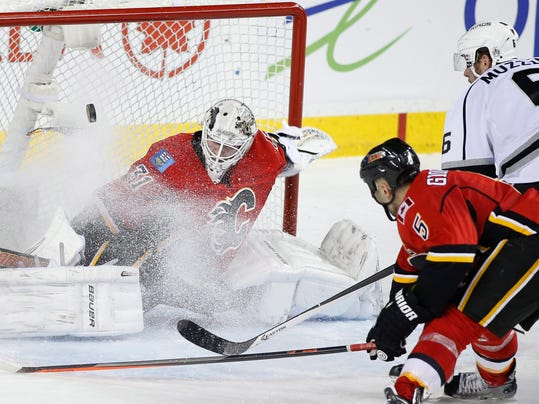 Calgary Flames goalie Karri Ramo, left, from Finland, makes a save against Los Angeles Kings' Jake Muzzin, right, as Flames' Mark Giordano defends during the third period of an NHL hockey game in Calgary, Alberta, Wednesday, April 9, 2014. (AP Photo/The Canadian Press, Larry MacDougal)