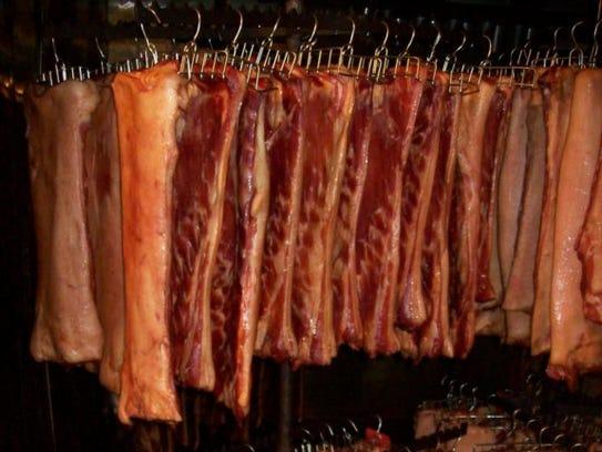 Slabs of bacon hang during the smoking process.