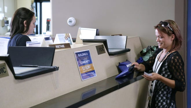 Michelle Graszl talks to Ashley Hall, a teller at the Richland Bank branch on Ashland Road. The bank has recently been remodeled and now has extended business hours.