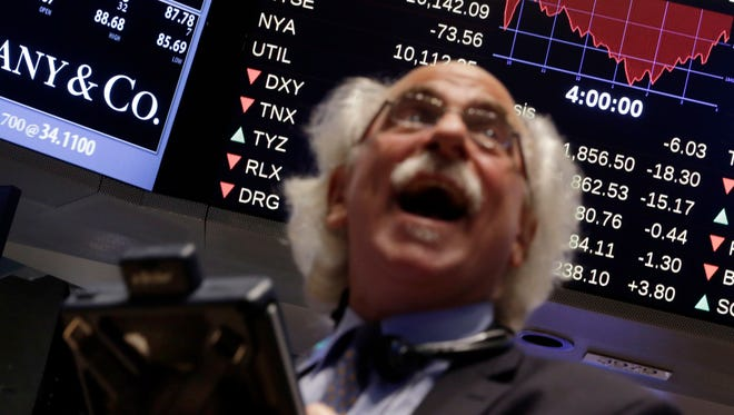 Trader Peter Tuchman watches a screen above the floor of the floor of the New York Stock Exchange at the closing bell, Wednesday, Oct. 15, 2014.