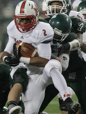 Cincinnati LaSalle's Jarell White, left, is tackled by Macedonia Nordonia's Alex Anders, center, and Vincent Hudson on Dec. 5, 2014, in Columbus, Ohio.