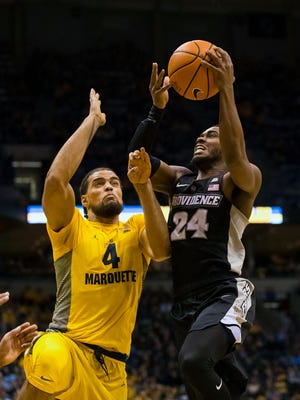 Marquette freshman Theo John goes up to block the shot of Providence guard Kyron Cartwright.