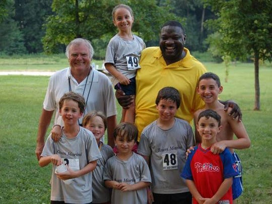 Howard Laws (back row, right) and Summer Running Series co-director Terry Mance pose with some younger runners after a 5K at Bellevue State Park. Laws will receive the DSBA's Herm Reitzes Service Award.