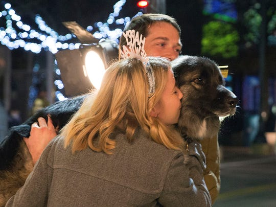 Before the chile dropped at the Plaza de Las Cruces, Hayley MacDonald kisses Moose her dog as Gordon MacDonald holds him and they pose for a photo at Paul Neff's Photo Booth set up in the Plaza, December 31, 2016.