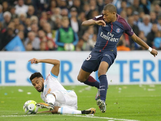 Marseille's Jordan Amavi, left, challenges for the ball with PSG's Kylian Mbappe during the League One soccer match between Marseille and Paris Saint-Germain, at the Velodrome stadium, in Marseille, southern France, Sunday, Oct. 22, 2017. (AP Photo/Claude Paris)