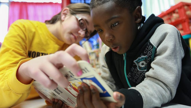 William Graves 5 of Detroit reads a book with tutor Maddie Stang of Faith Covenant Church of Farmington Hills on Monday March 30, 2015 at Mission: City in Detroit.