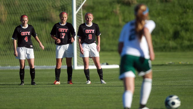 City High's Delaney Johnson, from left, Grace Brown and Sydney DePrenger line up to defend a free kick during their game against West High at the Iowa Soccer Complex on Monday, May 18, 2015.