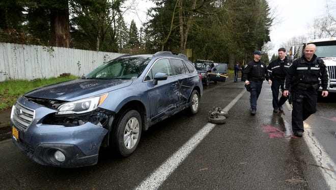Emergency personnel work to clean up Verda Lane near Salem Parkway in Keizer after the driver of a stolen car crashed into two police vehicles on Wednesday, March 9, 2016.