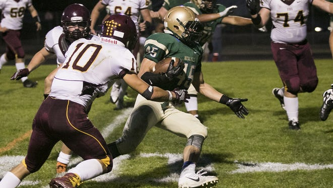 McKay's Matthew Jarding breaks through tackles from Forest Grove defense in the first half of a game on Friday, Sept. 16, 2016. The McKay Royal Scots won the game 43-0.
