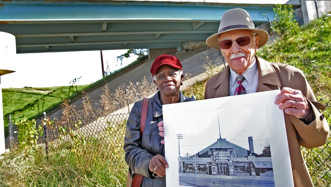 Beatrice Miller, left, and Judge William Levy take a walk down memory lane, Friday, Oct. 21, 2016, standing on South Meridian underneath I-70 in Indy's Southside.  They grew up in the area, which was unusually integrated. The neighborhood was decimated in the 1970s by the construction of I-70.  In this photo, they hold a photo of the Oriental Theater, which had been in that location.