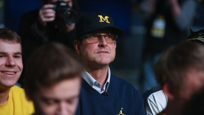 Michigan head coach Jim Harbaugh sits with students before the Signing of the Stars event at the Crisler Center in Ann Arbor on Wednesday, Feb. 1, 2017.
